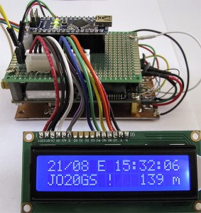 Een sandwich bestaande uit een printje met de Arduino Nano, een Jupiter GPS-ontvanger en onderop een printplaatje met een back-upbatterij en een 5V-stabilisator voor de Jupiter. Op de voorgrond een 16x2 lcd.