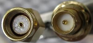 Rechts het 'verkeerd om' male SMA-contact; links een gemodificeerde SMA-connector die nu daarop past